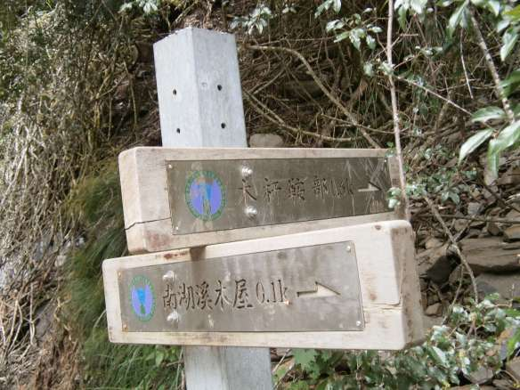 At the bottom of the valley the stream meets a river, where a signpost indicates the direction to continue.