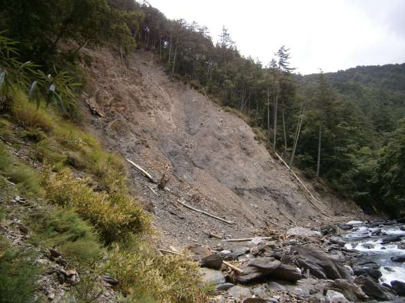 More landslide aftermath along the riverbank.