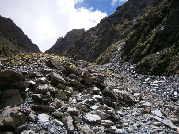 A scree slope leads to the mountain above the river.