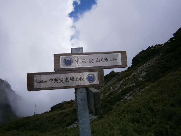 A signpost marks the saddle at the top of the scree slope.