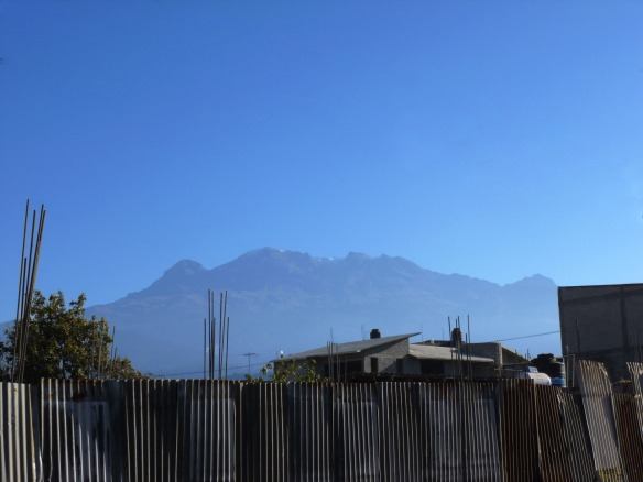 Iztaccihuatl, as viewed from the central square in Amecameca – the profile of the sleeping woman is clear in the photo: head and hair to the far left, legs and feet to the far right.