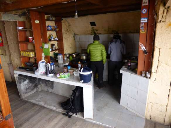 My mountain guide Pato and Fredy the refuge guardian in the cabin's kitchen.